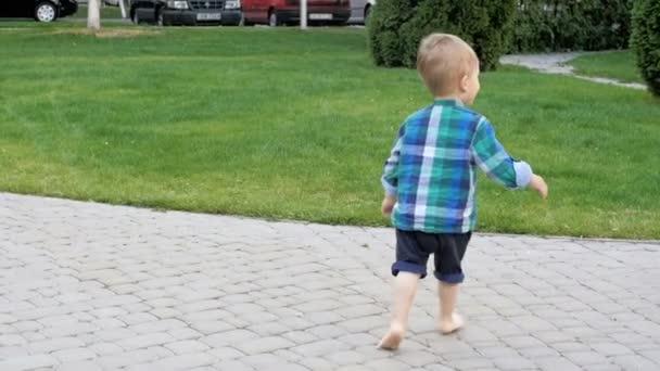 Zeitlupenvideo von entzückendem barfüßigen Kleinkind, das auf Fußweg im Park läuft