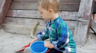 Slow motion footage of cute blonde toddler boy digging sand with plastic toy shovel at park