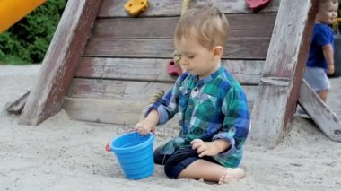 Slow motion video of cute toddler boy digging hole in sandbox on playground at park