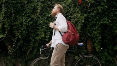 4k video of stylish young bearded man with bag walking with bicycle on street