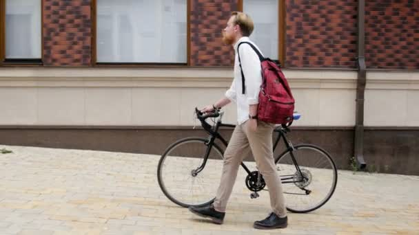 4 k videa stylové hipster člověka s červenou bradku chůzi na staré ulici s vintage černé kolo
