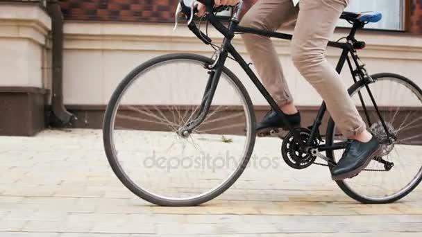 4 k nízkým úhlem záběru stylové hipster muž na koni černé sportovní kolo na ulici