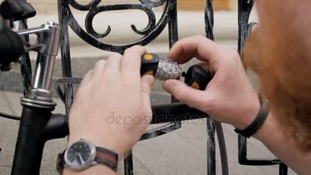 Closeup 4k záběry mladého muže pomocí kombinace lock a řetěz k ochraně jeho kolo na ulici