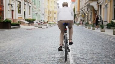 Slow motion footage of young man commuting to work on vintage sport bicycle