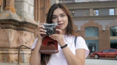 Slow motion video of smiling brunette tourist girl walking and making photos with old film camera