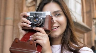 Closeup slow motion video of smiling tourist girl pressing shutter button on vintage film camera