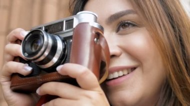 Closeup slow motion footage of beautiful young woman pressing shutter button on old camera