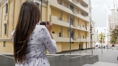 Slow motion video of stylish young woman making photographs with old camera