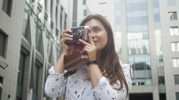 getönte Zeitlupenaufnahmen lächelnder Fotografinnen mit Vintage-Filmkamera