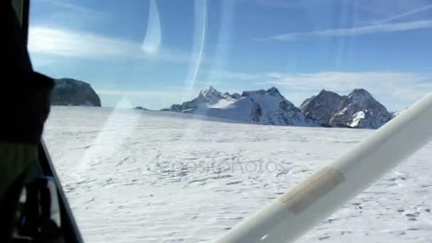 Aufnahmen aus dem Inneren eines kleinen Privatflugzeugs, das bei sonnigem Wetter über schneebedeckte Berge fliegt