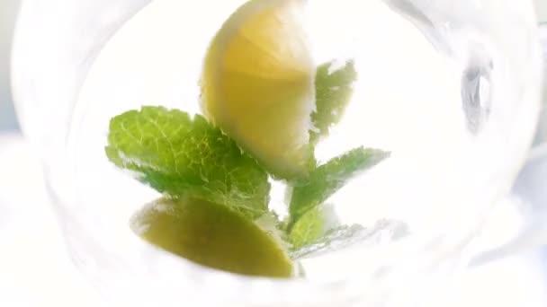 Pohled z vrcholu na plátky citronu, kostky ledu a listy máty otáčení a plovoucí ve velké skleněné