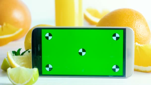 Nahaufnahme 4k Filmmaterial von Mobiltelefon mit grünem Bildschirm mit Chroma-Schlüssel, der auf einem Tisch neben einem Glas Saft mit frischen Früchten steht. perfekt für Ihre kulinarische oder gesunde Lebensmittelwerbung