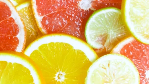 View from top of camera panning along assortment of citrus slices lying on table