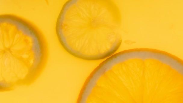 Closeup 4k footage of citrus slices floating in fresh orange juice