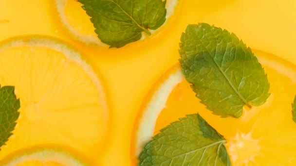 Macro footage from top view of fresh lemonade with mint and oranges