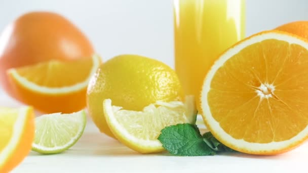 Closeup footage of oranges, limes, lemons and glass of orange juice on wooden table