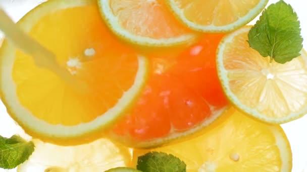 Detailní zpomalené video lití orenge šťávy do sklenice plné plátky citrusů a máty