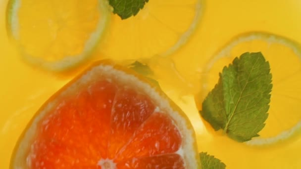 Slow motion video of grapefruit slice falling in jar with orange juice and mint