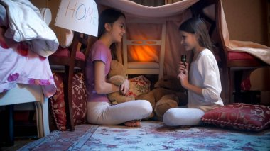 Two smiling girls playing in selfmade tent and telling stories at night