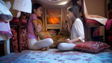 Two cute girls in pajamas playing in tent made of blankets and telling stories