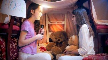 Two cute girls in pajamas telling stories at dark night
