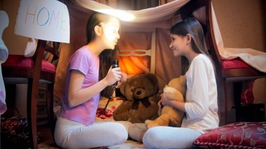 Two cute girls having pajamas party at night and telling stories