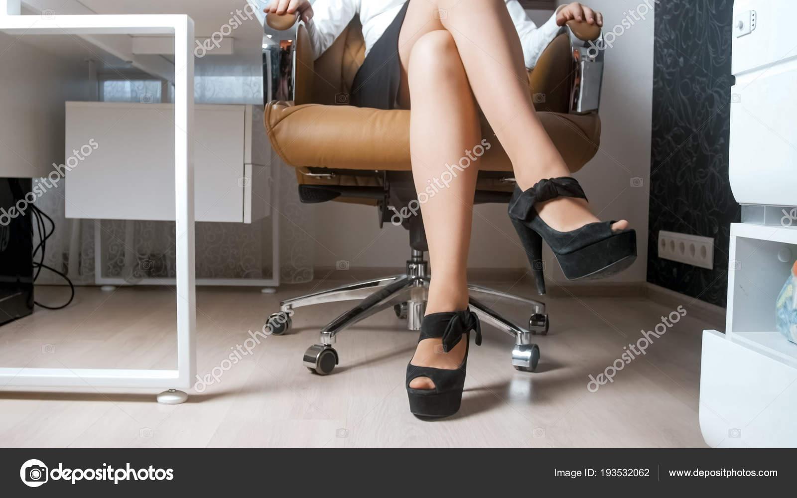 5913e6ecf493 Sexy mujer joven vestida con zapatos de tacones y falda corta, sentado en  la silla