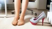 Fotografie Junge weibliche Büroangestellte zog high Heels Schuhe unter Tisch