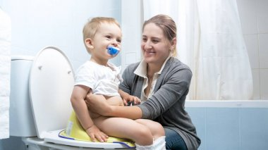 Young smiling mother with her toddler boy sitting on toilet