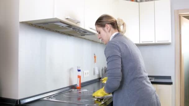 4 k Video Hausfrau in Latex Handschuhe Spritzen Reinigungsmittel über Elektro-Kochfeld und Waschen mit Schwamm