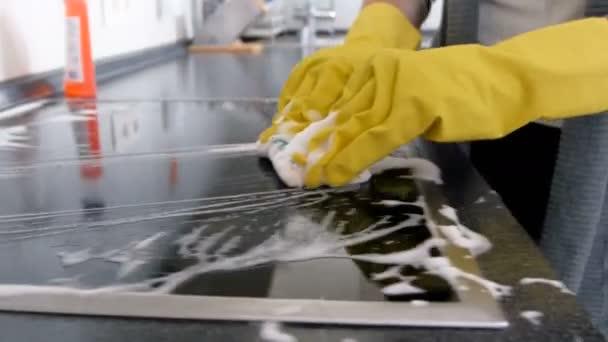 Nahaufnahme 4k Filmmaterial von jungen Hausfrauen in Latexhandschuhen, die Elektroherde in der Küche mit Waschmittel und Schwamm waschen