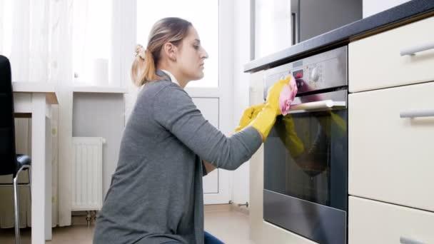 4k Filmmaterial der jungen lächelnden Hausfrau, die die Glastür des Elektrobackofens in der Küche reinigt