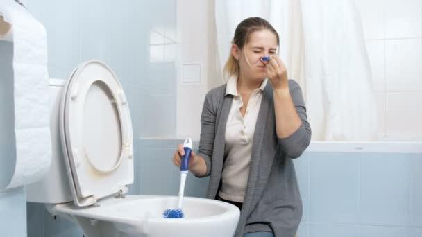 4k Filmmaterial von zimperlicher junger Frau, die ihre Nase schließt, während sie zu Hause die schmutzige Toilette wäscht