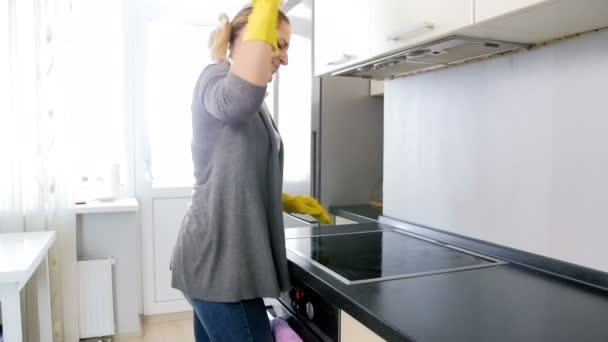 Slow-Motion-Video von Exhaisted böse Hausfrau unter off gelbe Gummihandschuhe und Schreie während der Hausarbeit