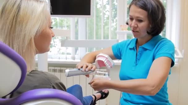 4k video of dentist teaching her patient how to clean teeth with electric brush