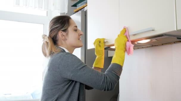 4k Video einer lächelnden jungen Frau in Latex-Handschuhen, die Schränke in der Küche mit Tuch säubert