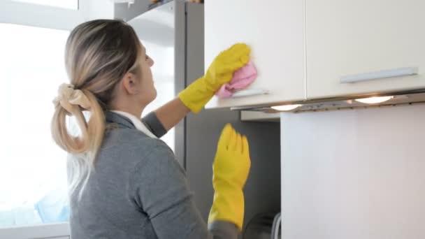 4 k video Mladá hospodyně, leštění a čištění skříně v kuchyni