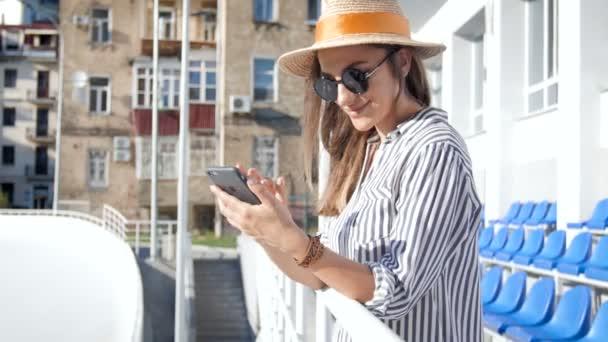 4k-Video einer glücklich lächelnden Frau mit Sonnenbrille und Hut mit Smartphone auf der Straße