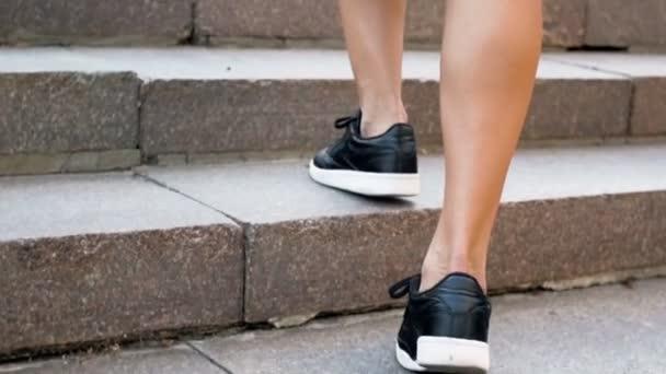 Detailní zpomalené záběry ženské nohy v černé kožené tenisky, chůzi po schodech na ulici