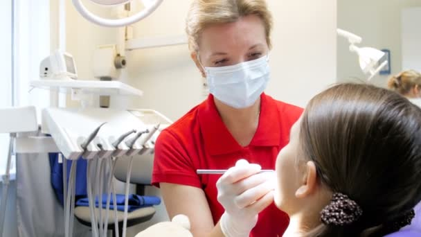 4k video of female dentist examines girls oral cavity in dental clinic
