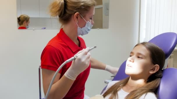 4k footage of female dentist removing caries with dental drill from teenagers teeth