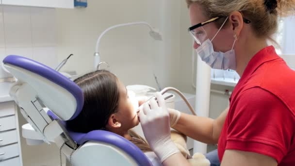 Closeup 4k footage of female dentist treating teenage girl in dental clinic