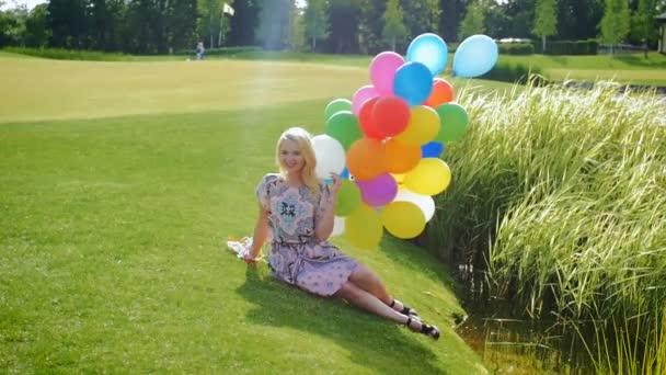 Slow motion záběry šťastná mladá žena v šatech sedí na trávě s balónky