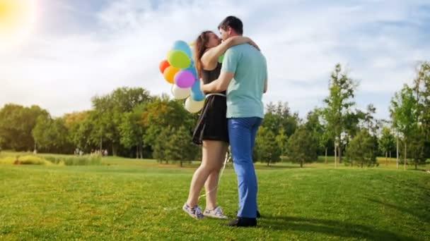 Zeitlupenvideo von schönem jungen Paar mit vielen bunten Luftballons und Umarmungen im Park
