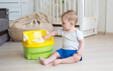 Adorable toddler boy looking at toilet baby pot