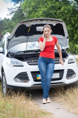 Young woman leaning on broken car with open hood and calling car assistance service