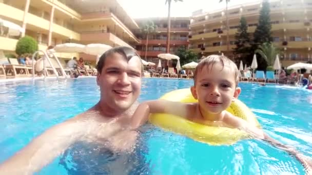 Slow motion video of happy smiling and laughing father with little son swimming in outdoor swimming pool at hotel resort
