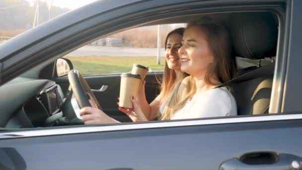 4k video of two happy smiling women drinking coffee while riding a car on sunny day