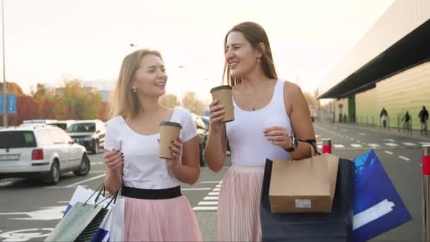 4k video of two laughing female friends walking out of shopping mal with lots of paper bags and drinking coffee