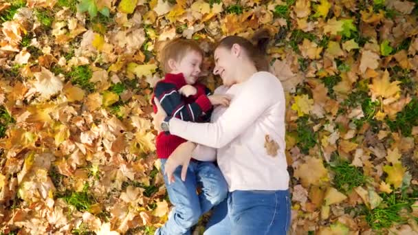 4k video of little toddler boy with mother playing, tickling each other, hugging and kissing while lying on yellow leaves and grass in autumn park